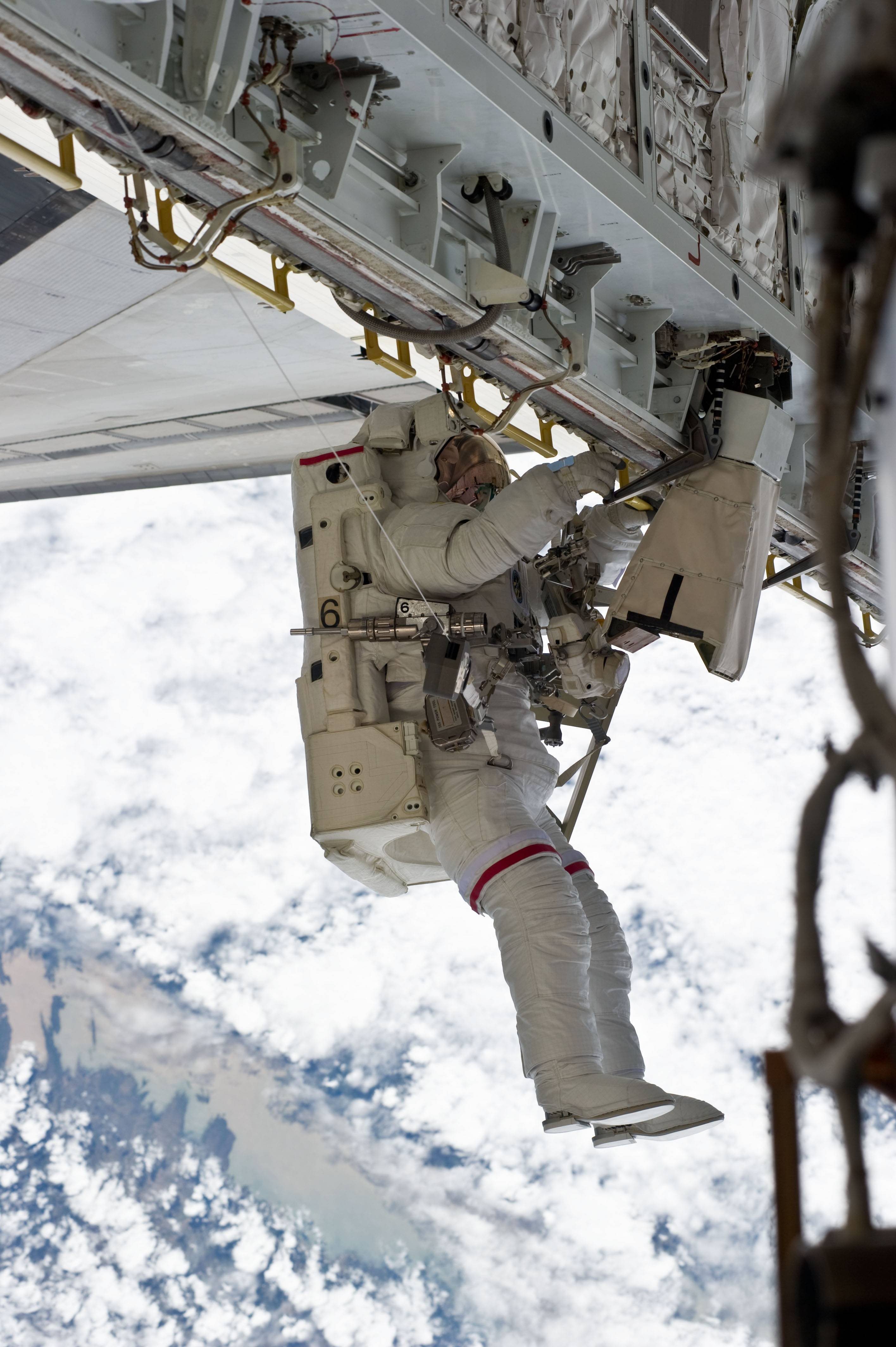 Astronaut Rick Mastracchio working with a SAFER system attached.